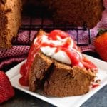 A slice of chocolate angel food cake topped with whipped cream and strawberry sauce on a square white plate next to strawberries and the rest of the cake on a cooling rack
