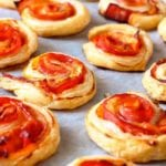Puff pastry bacon pinwheels with cheddar cheese on parchment paper on a baking sheet
