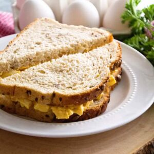 A deviled egg salad sandwich cut diagonally in half on a white plate next to fresh parsley and a carton of eggs
