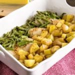White casserole dish of green beans, chicken, and potatoes sitting on a red kitchen towel