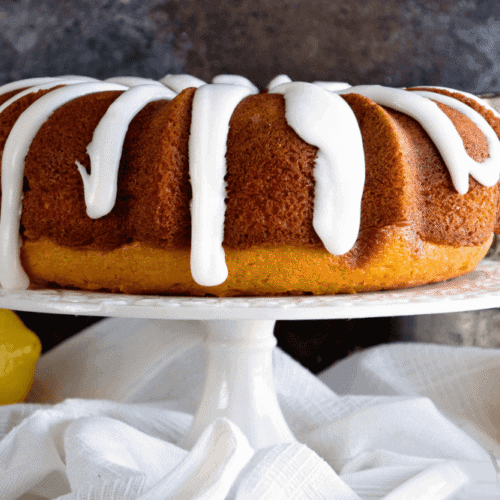 Lemon bundt cake with icing on a white cake stand over lemons on a white kitchen towel