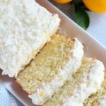 A partially sliced lemon and coconut loaf cake on a white tray