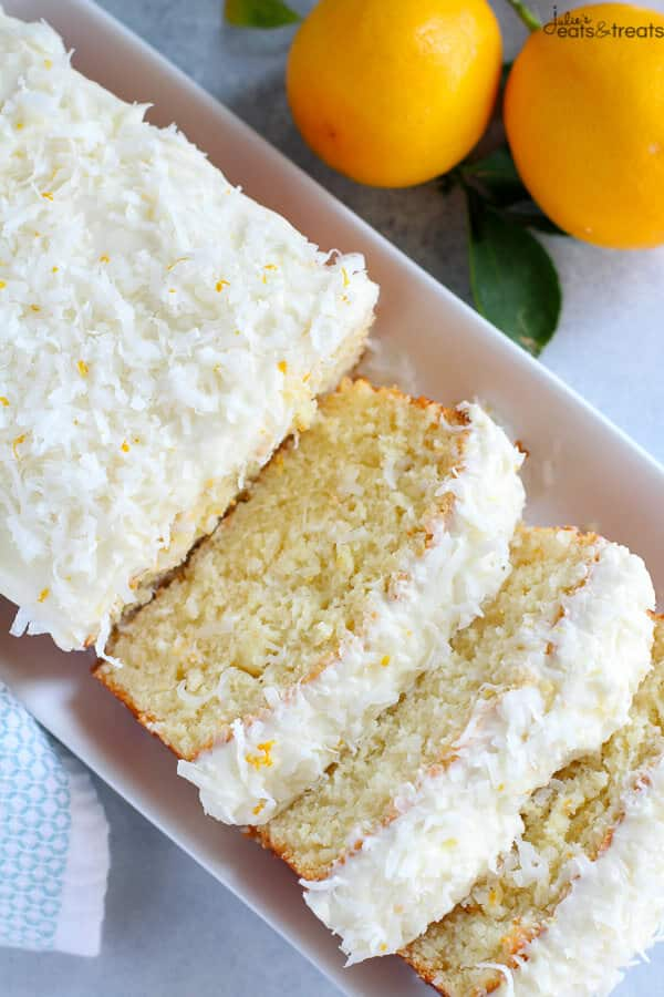 A sliced lemon coconut cake on a white serving platter with lemons in background.