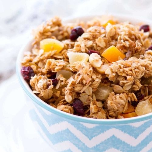 A blue and white chevron bowl of tropical coconut granola sitting on a white plate