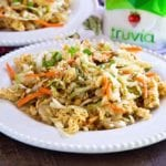 Two white plates loaded with Asian ramen salad on a wood table next to a jar of truvia