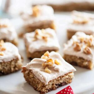 Banana nut bars on a white cake stand with a red ribbon around the base