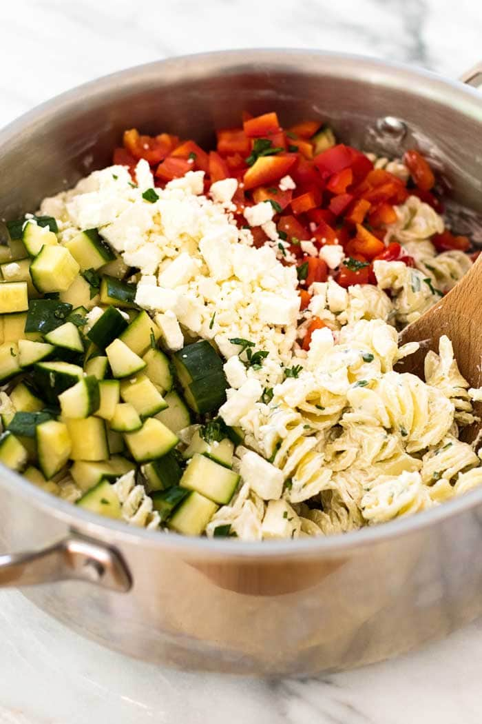 All the ingredients for this cold pasta salad recipe; Bell Pepper, Cucumber, Pasta and Topped with a Creamy Yogurt Dressing in a large bowl ready to be mixed.