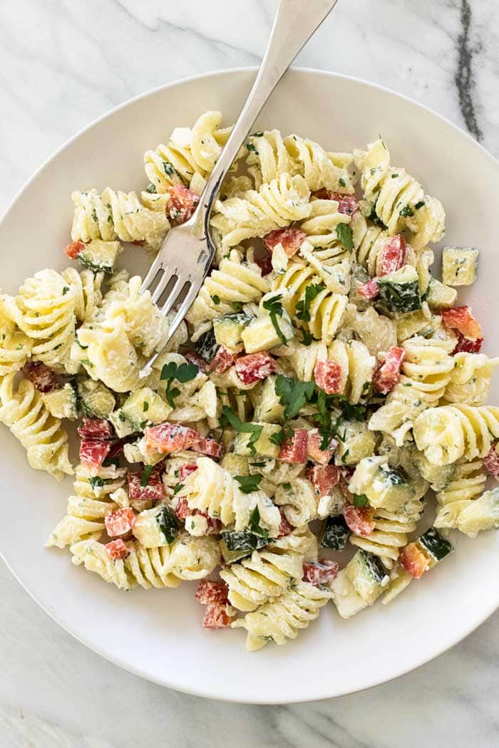 Overheat picture of Greek Pasta Salad on a white plate with a fork.