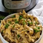 White bowl of hamburger stroganoff sitting in front of an instant pot