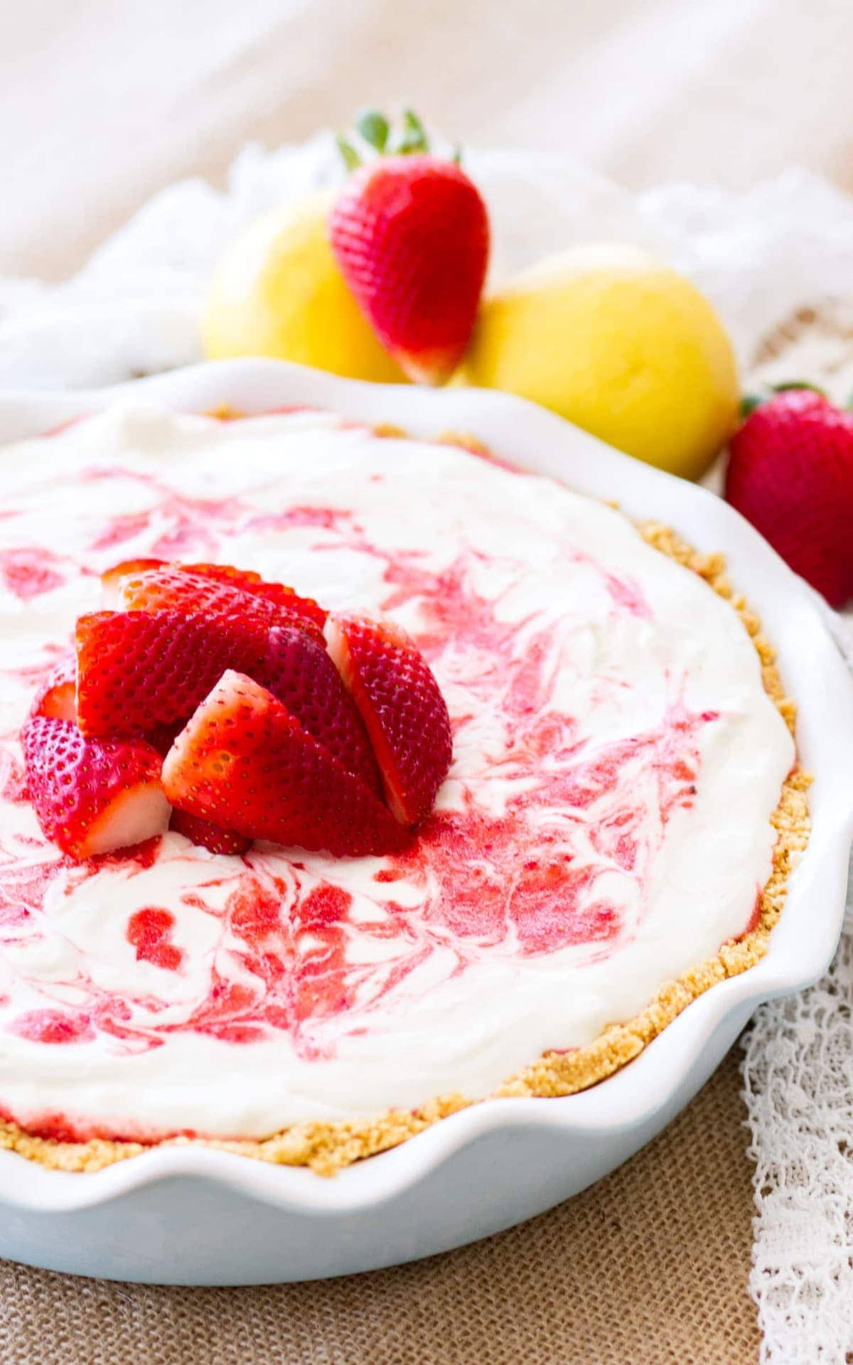 Strawberry Lemonade Pie surrounded by strawberries and lemons. This icebox pie is sweet, a little tangy, and the perfect no-bake dessert for summer!