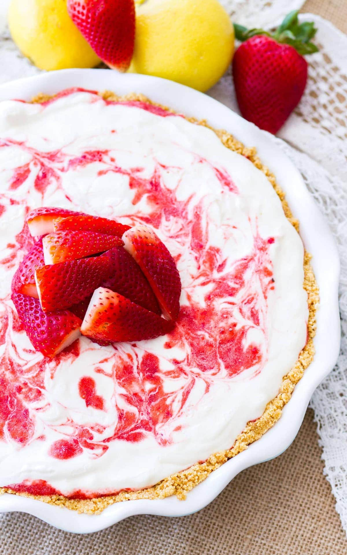 An overhead picture of Frozen Lemonade Pie in a white pie tin surrounded by strawberries and lemons. Strawberry lemonade icebox pie is a perfect no-bake dessert for summer!