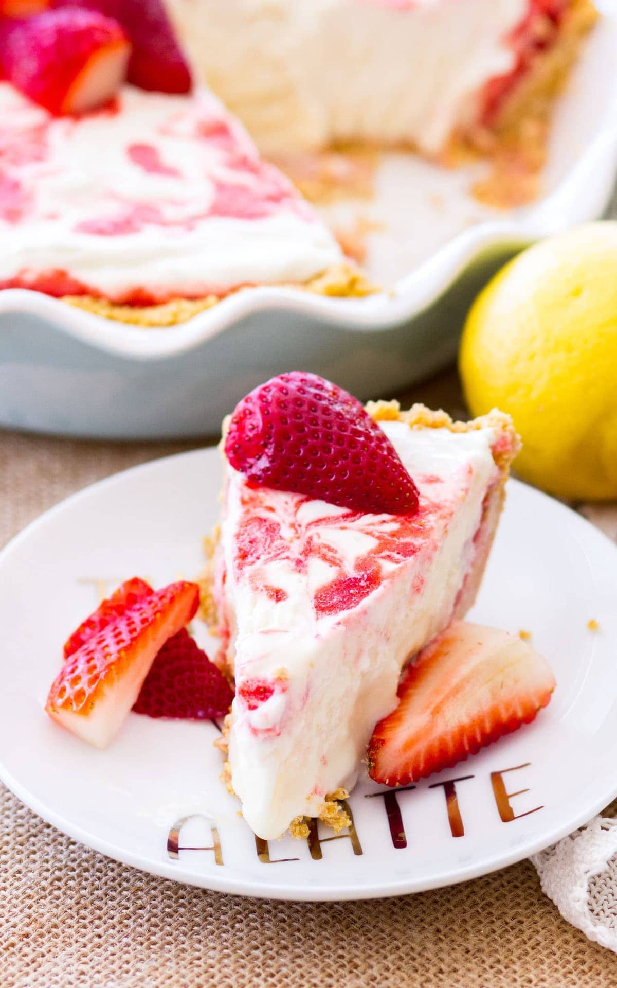 A slice of Strawberry Lemonade Pie on a white plate. The rest of the Strawberry lemonade icebox pie is just behind the slice waiting to be served.