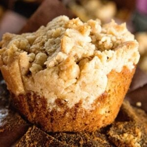 Up close image of a crumb banana muffin sitting on a brown paper muffin liner
