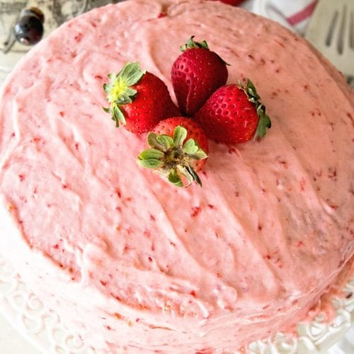 Easy fresh strawberry cake sitting on a white cake stand topped with four whole strawberries