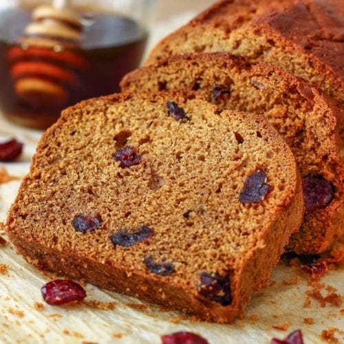 Slices of honey cranberry bread on a table with a glass jar of honey