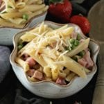 Two bowls of instant pot ham and penne pasta with shredded cheese and peas sitting on a towel with a wooden spoon and strawberries