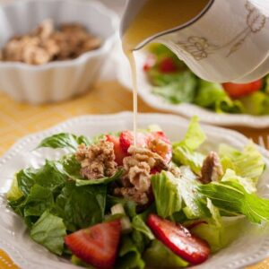 Strawberry romaine salad in a white bowl with dressing being poured over the top