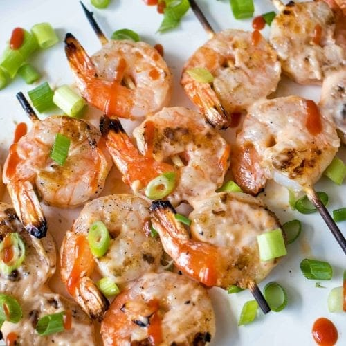 Row of shrimp kebabs on a white plate with green onions