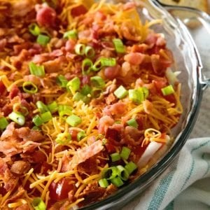 Easy BLT dip in a clear glass pie plate sitting on a white kitchen towel