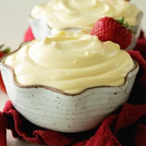 Two cream bowls of easy vanilla pudding with strawberries on a red kitchen towel