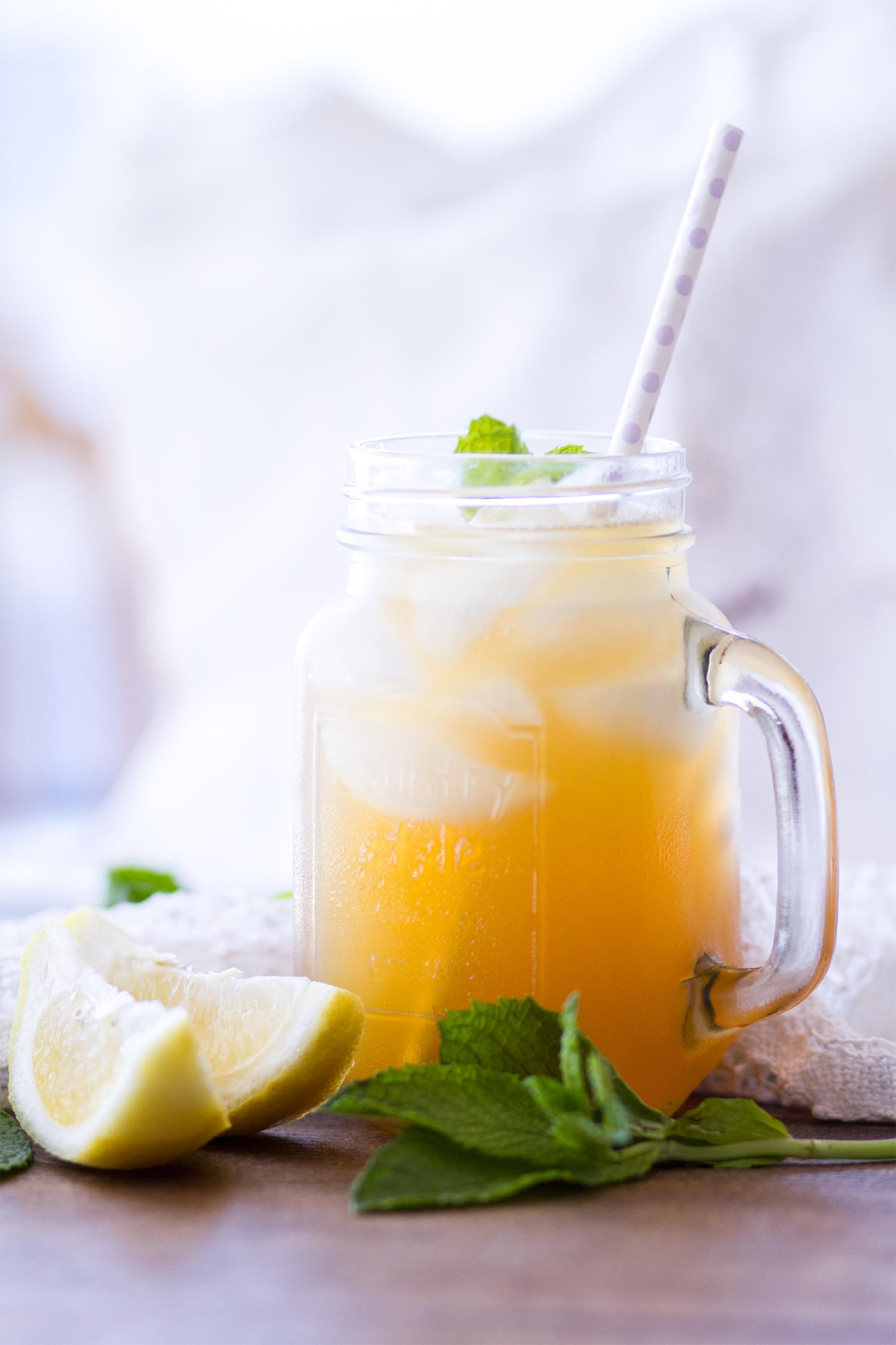 A mason jar glass filled with iced tea, ice cubes, a sprig of mint and paper straw on a wooden background with lemon slices and mint next to it.