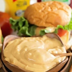 Stacked brown bowls with burger sauce in the top one in front of a cheese burger and bottles of mustard and ketchup