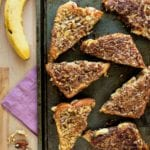 Seven triangular halves of banana nut stuffed french toast on a baking sheet sitting on a wood table with a purple napkin, pecans, and bananas