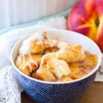 Blue bowl of cinnamon roll peach cobbler on a table with a white cloth and a peach