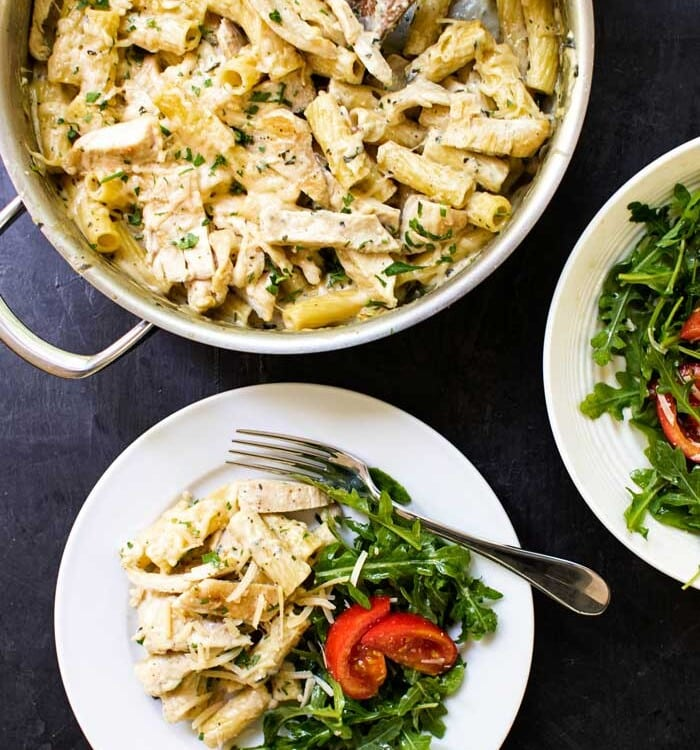 Creamy pesto chicken pasta in a pot and on a white plate with salad