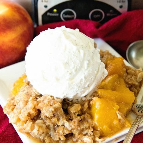 Peach cobbler with a scoop of vanilla ice cream on a square plate in front of a crock pot
