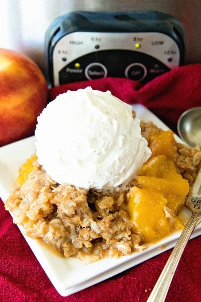 Crock Pot Peach Cobbler dished up onto a white plate, topped with a dollop of ice cream.