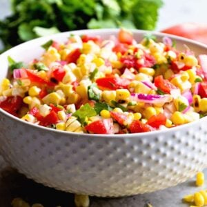 A white bowl of grilled corn salsa next to tortilla chips, cilantro, tomatoes, limes, and corn