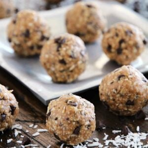 No bake chocolate chip energy bites on a table and on a silver plate sprinkled with coconut flakes and mini chocolate chips