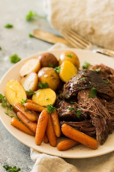 CRAZY TENDER, MELT IN YOUR MOUTH SLOW COOKER POT ROAST WITH CARROTS AND POTATOES. THIS SUPER EASY MEAL REQUIRES LITTLE PREP AND THE CROCKPOT DOES ALL THE WORK!