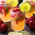 Three mason jars of strawberry limeade sangria with strawberries and limes slices in the glasses and on the counter