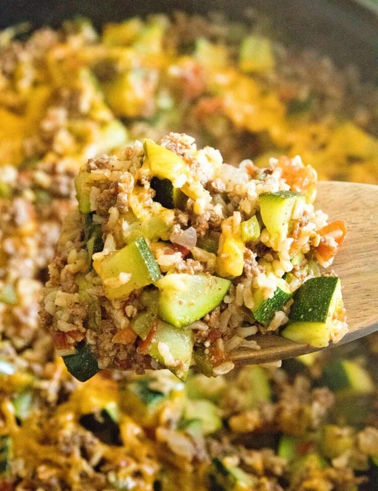 Wooden spoon scooping hamburger and zucchini skillet