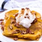Two pieces of baked pumpkin french toast on a white plate topped with syrup, pecans, whipped cream, and cinnamon