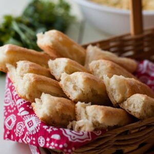 Breadsticks in a basket lined with red and white cloth
