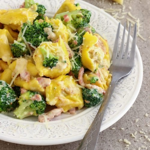 Broccoli tortellini on a white plate with a fork