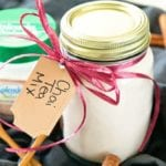 Mason jar of chai tea mix with ribbon and a label around the neck sitting on a black cloth with cinnamon sticks, a small wood spoon, and a container of splenda