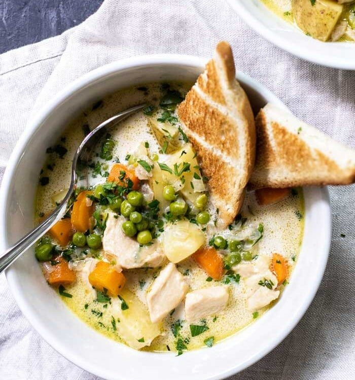 Overhead image of two white bowls of chicken pot pie soup with toast and a spoon in them on a white kitchen towel