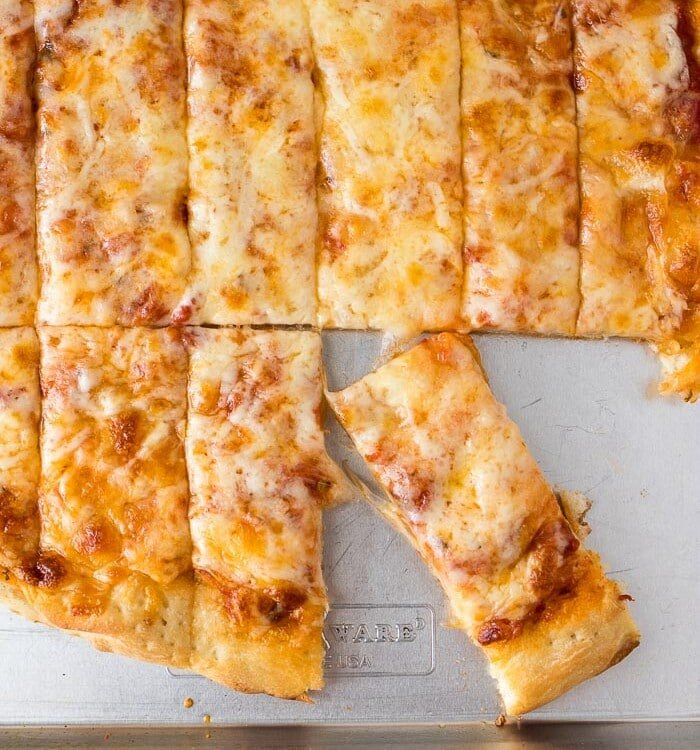 Overhead image of a batch of four cheese pizza dunkers on a metal sheet pan