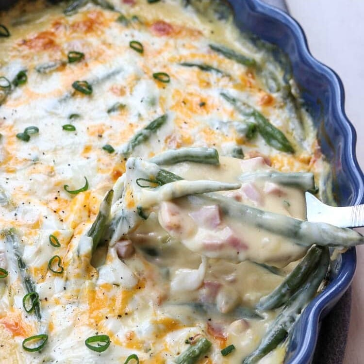Green beans and ham casserole in a blue baking dish with a spoon scooping some out