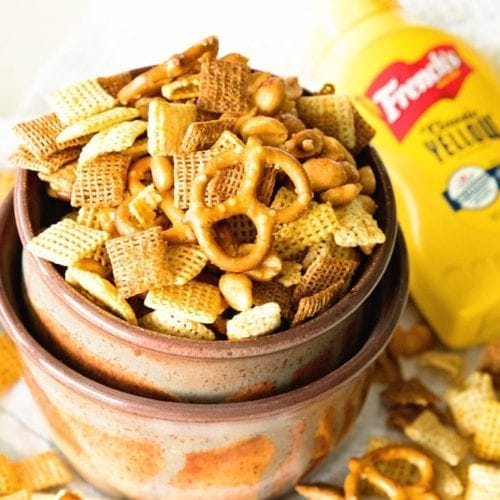 Brown bowl of honey mustard homemade snack mix spilling out onto a white kitchen towel underneath next to a bottle of mustard