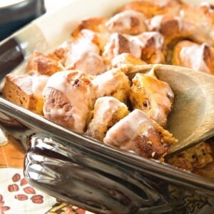Pumpkin cinnamon roll bake in a square baking dish with a wooden spoon scooping some out