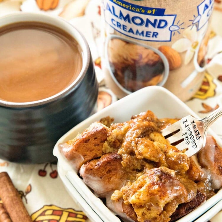 Pumpkin cinnamon roll bake in a small white bowl with a fork in it sitting on a thanksgiving themed table cloth with a bottle of silk creamer, a mug of tea, and some cinnamon sticks