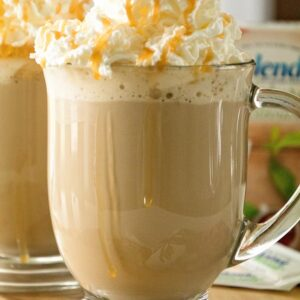 Glass mug of caramel latte with whipped cream topping and caramel drizzle