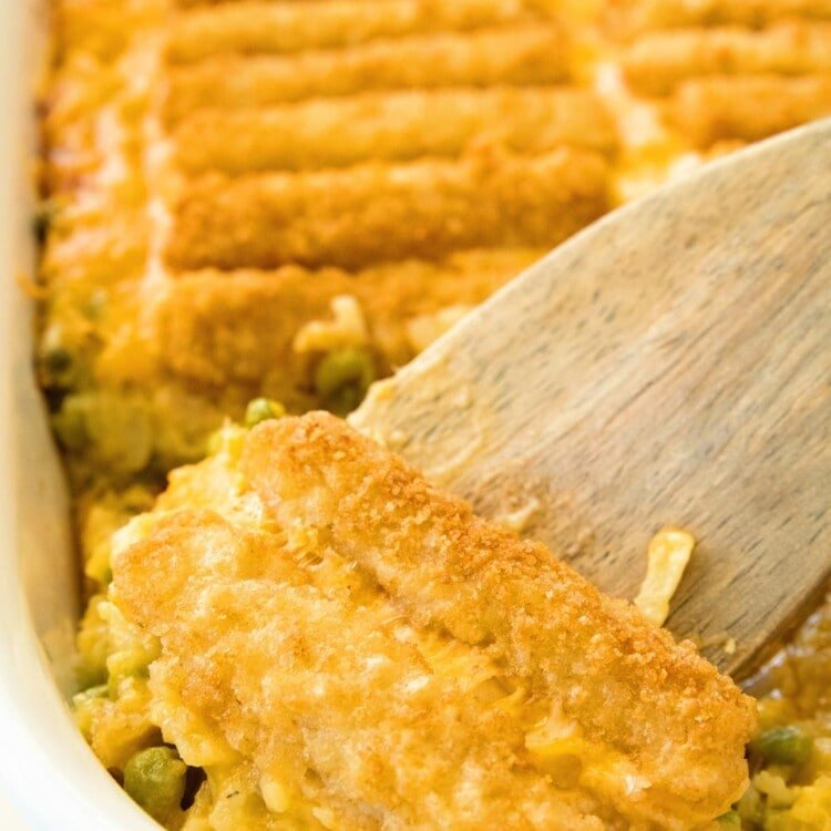 Cheesy Fish Stick Hash Brown Casserole in a white baking dish with a wood spatula