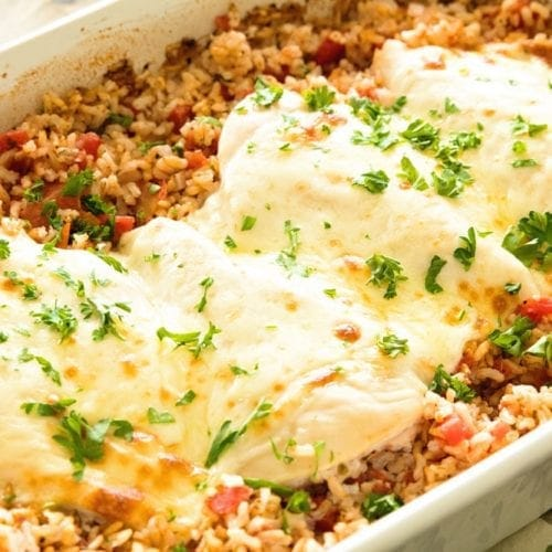 Cheesy Italian chicken and rice casserole in a white baking dish topped with fresh parsley