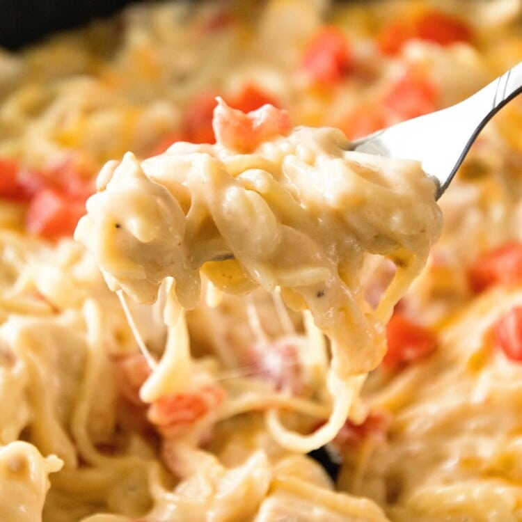 Fork full of cheesy one pot mexican spaghetti over a skillet of pasta